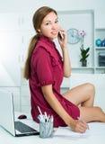 聊天在电话的女商人,当坐运转的书桌a时 库存照片