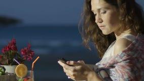 聊天在网上在智能手机的愉快的美丽的女性在室外餐馆 影视素材