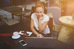 聊天在网络的可爱的妇女通过便携式的网书在咖啡店的早晨早餐期间 库存图片