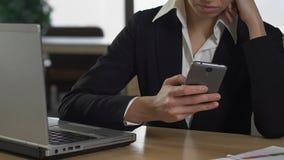 聊天在膝上型计算机智能手机坐的前面,技术的女性办公室工作者 股票录像