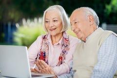 聊天在膝上型计算机的资深夫妇录影 免版税库存照片