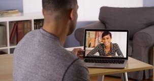 聊天在膝上型计算机的非洲朋友录影 免版税库存照片