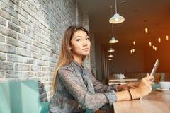 聊天在触摸板的典雅的女实业家,当坐在舒适的咖啡店时 库存图片
