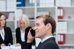 聊天在他的手机的愉快的商人 库存照片