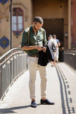 聊天在他的电话的有胡子的旅行家 免版税库存照片