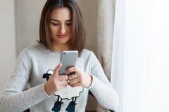聊天对她的电话的朋友和在家享受她的天的Youngsmiling妇女 库存照片