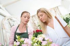 聊天对顾客的卖花人 免版税库存图片