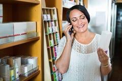 聊天由电话的妇女,当购物在药房时 免版税库存照片