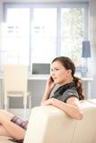 聊天的女孩移动性感的坐的沙发 免版税库存照片