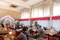 聊天的男人和妇女吃晚餐在与沙发的亚洲样式茶馆在中亚 免版税库存图片