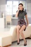 聊天的移动性感的坐的沙发妇女 库存图片