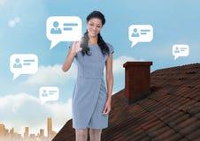 聊天站立在有烟囱和城市天空的屋顶的外形泡影和女实业家 免版税库存图片