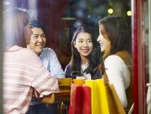 聊天谈话在咖啡店的四个年轻亚洲成人在嘘以后 库存图片