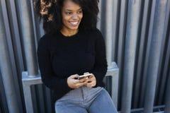 聊天通过在智能手机的应用的迷人的快乐的非裔美国人的妇女连接释放5G无线 免版税库存图片