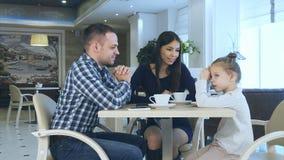 聊天witn女儿的愉快的年轻父母在他们的在咖啡馆饮用的茶的家庭度假时 库存图片