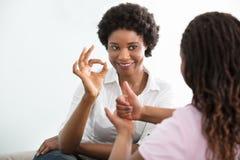 聋与她的女儿的母亲谈的手势语 免版税库存图片