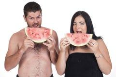 聋吃西瓜的男人和妇女 免版税库存照片