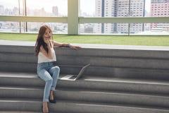 职业妇女使用电话和计算机膝上型计算机坐台阶 免版税库存照片