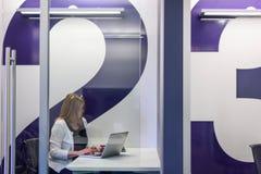 职业妇女在运作现代玻璃的办公室坐膝部 免版税图库摄影
