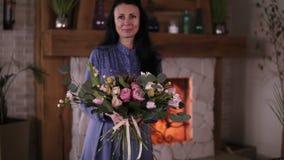 职业妇女花卉艺术家,拿着不同的玫瑰和叶子的美丽的花束蓝色礼服的卖花人在 股票视频