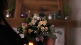职业妇女花卉艺术家,拿着玫瑰,在淡色coloures的郁金香的美丽的花束卖花人在车间 影视素材