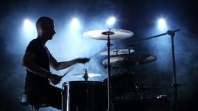 职业音乐家演奏在鼓的音乐 发烟性的背景 侧视图 剪影 回到光 影视素材