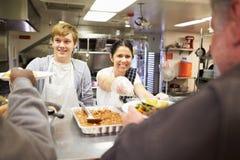 职员服务食物在流浪者避身处厨房里 库存图片