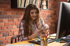 职场的键入消息的年轻美好的女性desiner或形象艺术家电话的 免版税库存照片