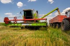 联合收割机卸载麦子入拖拉机 库存照片