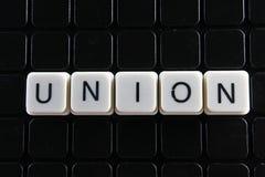 联合文本词标题说明标签盖子背景背景 字母表信件在黑反射性背景的玩具块 白色Al 免版税库存图片