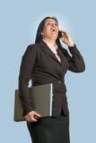 联系在电话和拿着膝上型计算机的女实业家 免版税库存图片