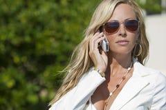 联系白肤金发的移动电话的太阳镜妇&# 免版税图库摄影
