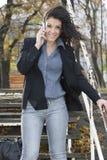联系的女实业家在公园移动电话。 免版税库存照片