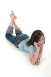 联系6个移动电话的女孩青少年的年轻& 免版税库存照片