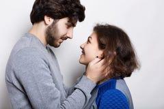 联系和感觉 轻轻地接触他的girfriend ` s面孔的有胡子的行家 看彼此的一对愉快的夫妇` s注视与gre 免版税库存图片