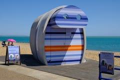 聘用的明亮的strippy现代海滩小屋在伊斯特本海滩 承担一个明亮的天空蔚蓝夏天的下午 库存图片