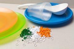 聚乙烯粒子和一次性碗筷由聚乙烯,聚丙烯制成 塑料原材料和它的产品 免版税库存图片