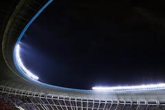 聚光灯和泛光灯在一个体育场在晚上 库存图片