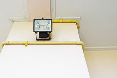 黑聚光灯电灯泡(选择聚焦)在奶油色colo被安装 库存图片