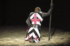 聚光灯的下跪的骑士 免版税库存照片