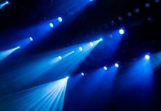 从聚光灯的蓝色光通过烟在表现期间的剧院 库存照片