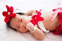 聚焦在有服装小的美人鱼的亚裔新出生的女婴在窗口旁边的红颜色与阳光 免版税库存图片