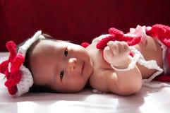 聚焦在有服装小的美人鱼的亚裔新出生的女婴在窗口旁边的红颜色与阳光 免版税图库摄影