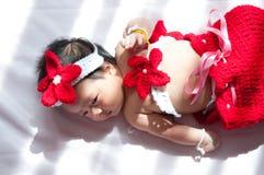 聚焦在有服装小的美人鱼的亚裔新出生的女婴在窗口旁边的红颜色与阳光 免版税库存照片