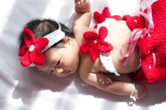 聚焦在有服装小的美人鱼的亚裔新出生的女婴在窗口旁边的红颜色与阳光 图库摄影
