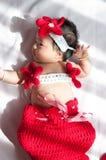 聚焦在有服装小的美人鱼的亚裔新出生的女婴在窗口旁边的红颜色与阳光 库存图片