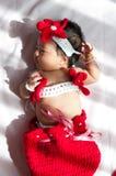 聚焦在有服装小的美人鱼的亚裔新出生的女婴在窗口旁边的红颜色与阳光 库存照片