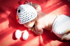 聚焦在有服装鸡的亚裔新出生的女婴用在窗口旁边的两个鸡蛋与阳光 免版税库存照片
