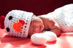聚焦在有服装鸡的亚裔新出生的女婴用在窗口旁边的两个鸡蛋与阳光 库存图片
