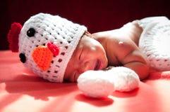聚焦在有服装鸡的亚裔新出生的女婴用在窗口旁边的两个鸡蛋与阳光 免版税库存图片